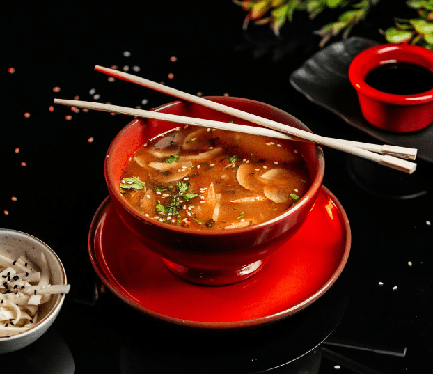 A bowl of miso soup with chopsticks on a table.