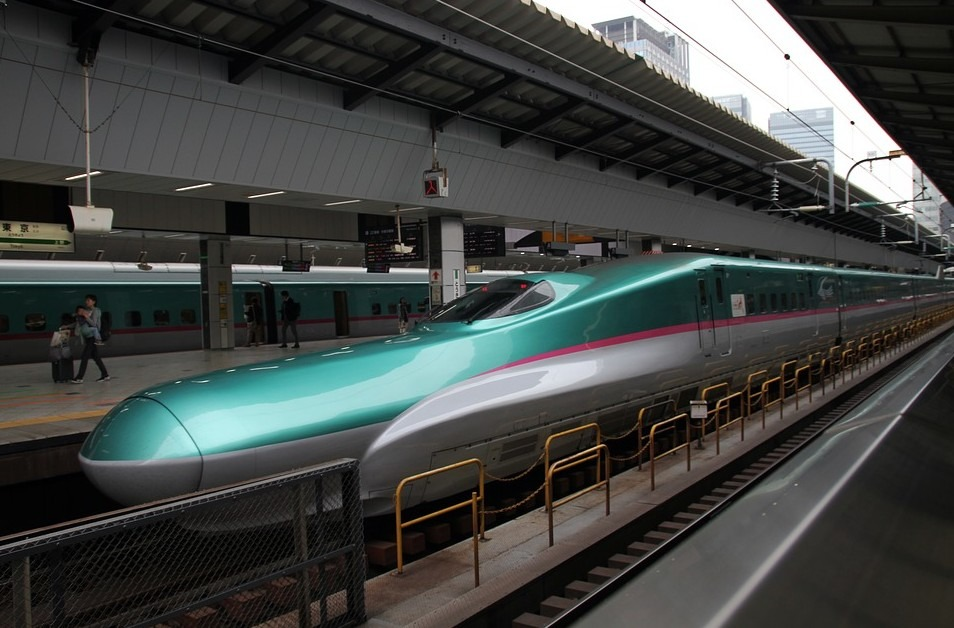 A green bullet train with people